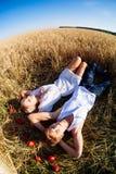 Imagem do homem novo e da mulher que encontram-se no campo de trigo Vista superior Foto de Stock Royalty Free