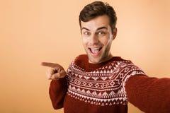 Imagem do homem novo 20s com a cerda que veste o poin feito malha da camiseta foto de stock