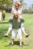 Imagem do homem sênior que dá o passeio do sobreposto da mulher fotografia de stock royalty free