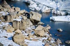 Imagem do inverno das rochas cobertas pela neve e pelo gelo na água Imagens de Stock Royalty Free