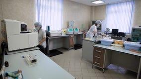 Imagem do laboratório médico com os dois assistans fêmeas da pesquisa que trabalham para dentro A enfermeira está sentando-se na  video estoque