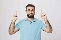 A imagem do meio considerável envelheceu o homem que sorri e que aponta seus dedos acima em uma pose feliz É tão aqui como a vitó fotos de stock royalty free