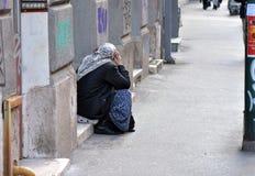 Imagem do mendigo fêmea que senta-se na caminhada lateral da rua vestida como a mulher muçulmana foto de stock royalty free