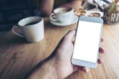 Imagem do modelo da mão que guarda o telefone celular branco com tela vazia e copos de café na tabela de madeira Imagem de Stock