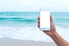 Imagem do modelo da mão do ` s da mulher que guarda o telefone celular branco com a tela vazia do desktop na frente do mar e do c Fotografia de Stock Royalty Free