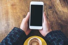 Imagem do modelo da vista superior das mãos que guardam o telefone celular branco com a tela preta vazia do desktop e o copo de c Imagem de Stock Royalty Free