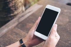 Imagem do modelo das mãos que guardam e que usam o telefone esperto branco com tela vazia Foto de Stock