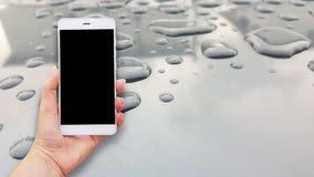 Imagem do modelo das mãos que guardam o telefone celular branco fotografia de stock