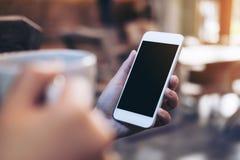 Imagem do modelo das mãos que guardam o telefone celular branco com a tela preta vazia ao beber o café Fotografia de Stock