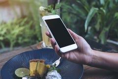 Imagem do modelo das mãos que guardam o telefone celular branco com a tela preta vazia ao comer o bolo amarelo do coalho de limão Foto de Stock