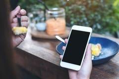 Imagem do modelo das mãos que guardam o telefone celular branco com a tela preta vazia ao comer o bolo amarelo do coalho de limão Fotografia de Stock Royalty Free