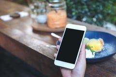 Imagem do modelo das mãos que guardam o telefone celular branco com a tela preta vazia ao comer o bolo amarelo do coalho de limão Imagem de Stock Royalty Free