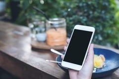 Imagem do modelo das mãos que guardam o telefone celular branco com a tela preta vazia ao comer o bolo amarelo do coalho de limão Fotos de Stock