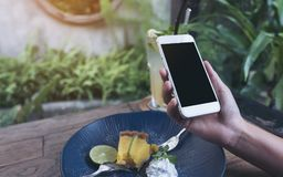 Imagem do modelo das mãos que guardam o telefone celular branco com a tela preta vazia ao comer o bolo amarelo do coalho de limão Imagens de Stock Royalty Free