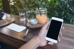 Imagem do modelo das mãos que guardam o telefone celular branco com a tela preta vazia ao comer o bolo amarelo do coalho de limão Imagens de Stock