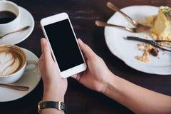 Imagem do modelo das mãos que guardam o telefone celular branco com a tela preta vazia com copos de café Fotografia de Stock Royalty Free
