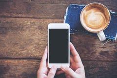 Imagem do modelo das mãos que guardam o telefone celular branco com a tela preta vazia com copos de café Imagens de Stock Royalty Free