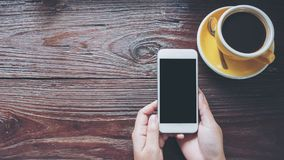 Imagem do modelo das mãos que guardam o telefone celular branco com a tela preta vazia com os copos de café quentes amarelos na t Fotos de Stock Royalty Free