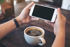 Imagem do modelo das mãos que guardam o telefone celular branco com a tela preta vazia para olhar e jogar jogos com uma xícara de Fotografia de Stock Royalty Free
