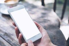 Imagem do modelo das mãos que guardam o telefone celular branco com a tela vazia na tabela de madeira do vintage Foto de Stock