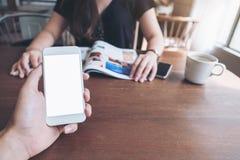 Imagem do modelo de uma mão do ` s do homem que guarda e que usa o telefone esperto branco com a tela vazia na tabela de madeira  fotografia de stock royalty free
