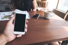Imagem do modelo de uma mão do ` s do homem que guarda o telefone celular branco com a tela preta vazia, os copos de café branco  Imagem de Stock