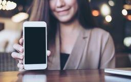 Imagem do modelo de uma mulher de negócio asiática bonita que guarda e que mostra o telefone celular branco com a cara preta vazi Foto de Stock Royalty Free