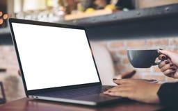 Imagem do modelo de uma mulher de negócios que usa o portátil com a tela branca vazia do desktop ao beber o café quente na tabela Imagem de Stock Royalty Free