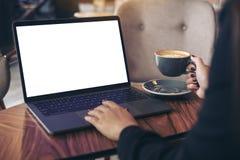 Imagem do modelo de uma mulher de negócios que usa o portátil com a tela branca vazia do desktop ao beber o café quente na tabela Foto de Stock Royalty Free