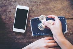 Imagem do modelo do telefone celular branco com a tela preta vazia e o jogo do girador da inquietação na tabela de madeira do vin fotografia de stock royalty free