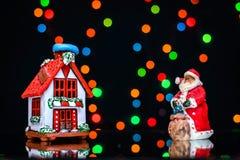 Imagem do Natal com Santa e casa em um fundo de luzes coloridas Imagem de Stock