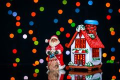 Imagem do Natal com Santa e casa em um fundo de luzes coloridas Foto de Stock