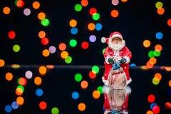 Imagem do Natal com Santa em um fundo de luzes coloridas Fotografia de Stock
