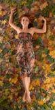 Imagem do outono com uma menina que encontra-se nas folhas caídas imagens de stock royalty free
