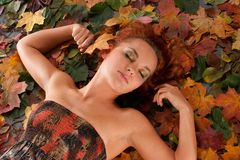 Imagem do outono com uma menina que encontra-se nas folhas caídas fotografia de stock