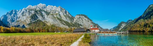 Imagem do panorama do Koenigssee com a capela de St Bartholomew e de um barco de turista No fundo a montanha iluminada fotos de stock royalty free