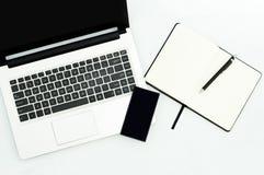 Imagem do portátil do computador, telefone celular, caderno vazio no local de trabalho imagens de stock royalty free
