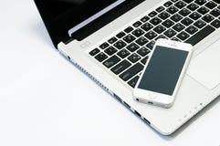Imagem do portátil do computador, telefone celular, caderno vazio no local de trabalho fotografia de stock