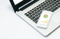 Imagem do portátil do computador, telefone celular com gráfico no local de trabalho imagem de stock
