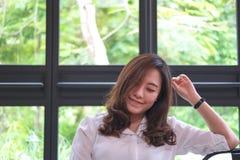 Imagem do retrato do close up da mulher asiática bonita com cara do smiley e do bom assento de sentimento no café com natureza ve fotografia de stock