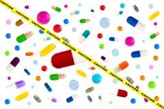 Imagem do símbolo do perigo das drogas: Muitas medicinas coloridas Comprimidos e cápsulas no fundo branco imagens de stock royalty free