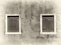 Imagem do Sepia da parede pintada afligida vintage com as duas janelas shuttered de madeira com bordadura brancas na luz solar br foto de stock