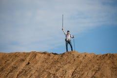 Imagem do turista do homem de longe com mãos acima com as varas para andar no monte Fotos de Stock