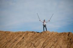 Imagem do turista masculino de longe com mãos acima com as varas para andar no monte Fotografia de Stock Royalty Free