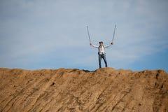 Imagem do turista masculino de longe com mãos acima com as varas para andar no monte Fotos de Stock