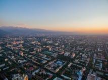 Imagem do zangão sobre a cidade no por do sol com montanhas fotografia de stock