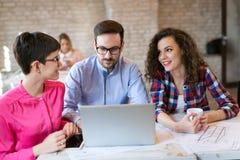 Imagem dos arquitetos novos que discutem no escritório fotos de stock