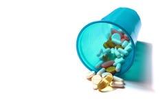 Imagem dos comprimidos diferentes que derramam fora de um vidro plástico Fotografia de Stock