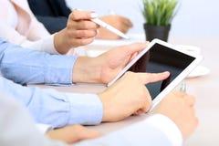 Imagem dos empresários novos que usam o touchpad na reunião Fotografia de Stock Royalty Free