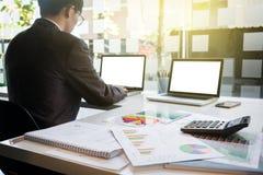 A imagem dos homens de negócios novos que usam o portátil com muitos documenta o gráfico fotos de stock royalty free